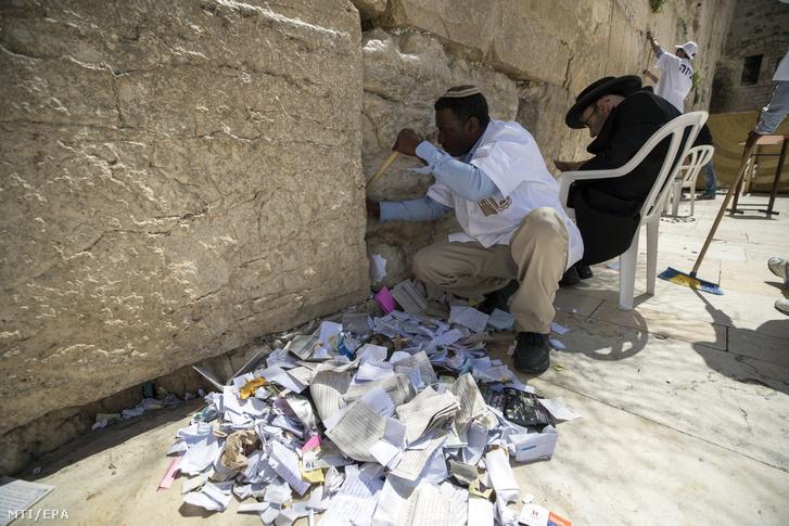 Ultraortodox zsidó férfi imádkozik a Siratófalnál, mialatt egy munkás a hívők által elhelyezett cédulákat távolítja el repedésekből Jeruzsálem óvárosában
