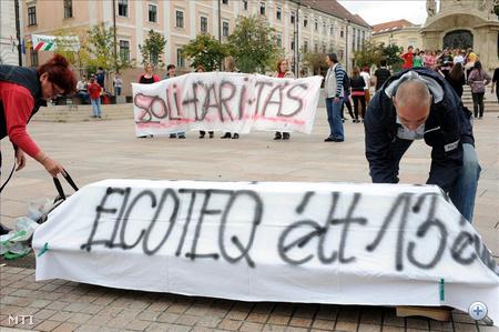 """A pécsi Széchenyi téren néhány száz ember gyűlt össze. Többen  transzparenseket tartottak a kezükben, mások egy koporsót hoztak, melyen az állt, hogy """" Elcoteq, élt 13 évet""""."""