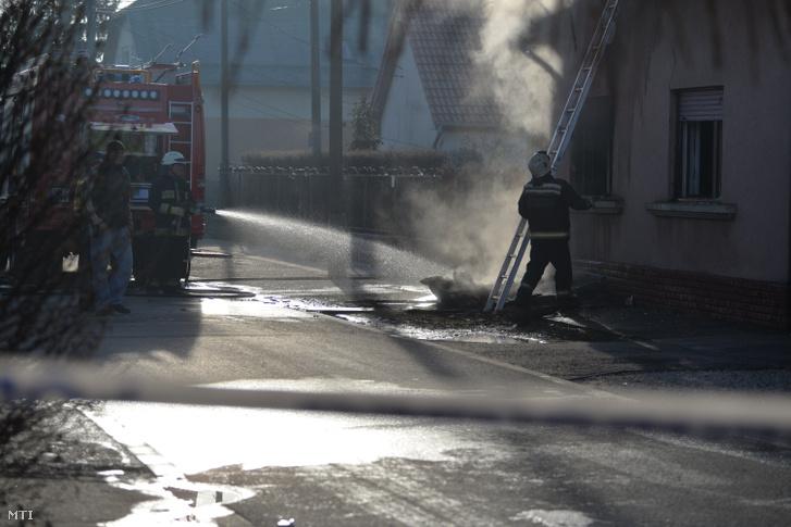 Tűzoltók dolgoznak egy családi házban keletkezett tűz oltásán a XVIII. kerületi Brigád utcában