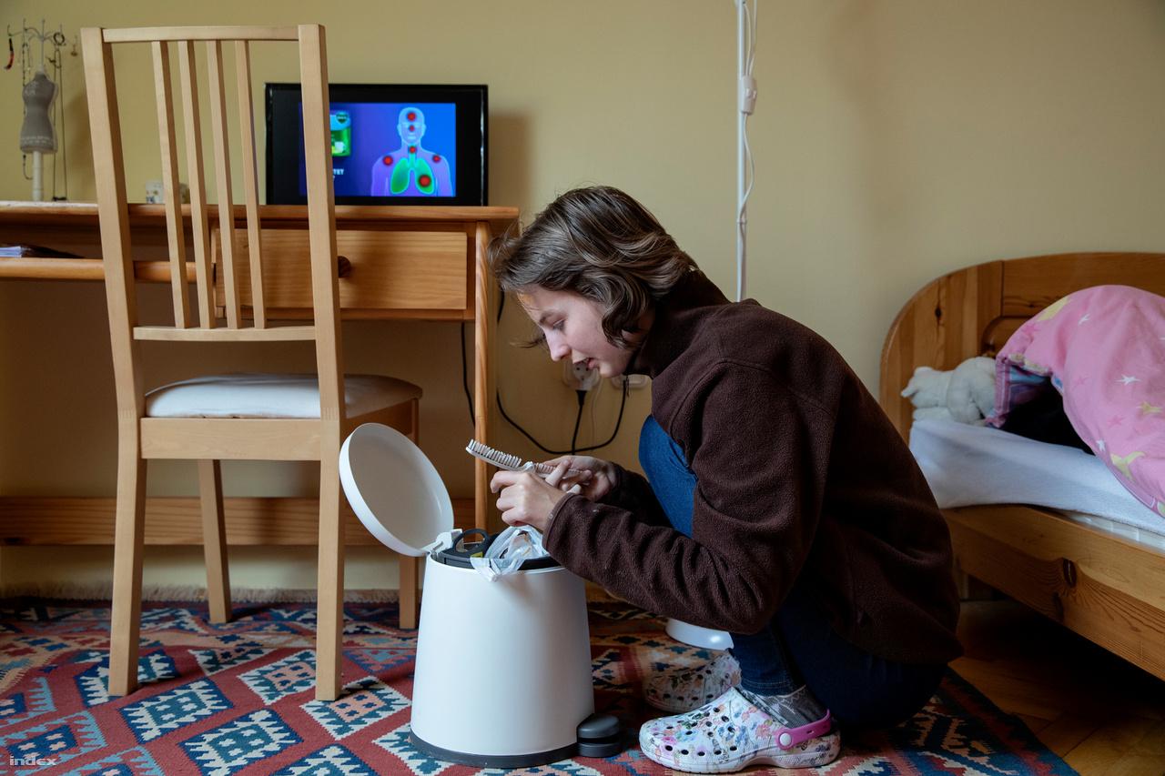 """Emese fésülködik a lakóotthon emeletén lévő szobájában (minden lakónak saját szobája van az emeleten, a közös tér a házban a földszinti konyha, ebédlő és nappali). A fésűben maradt hajszálakat akkurátusan, egyenként szedi ki a hajkeféből, és dobja szemétbe.MesevilágEmese 20 éves. 8 hónapos volt, amikor feltűnt, hogy valahogy másképp fejlődik. A hallására gyanakodtak, megvizsgálták, de hallott. Később nem indult be a beszéde, a mozgása is kevésbé fejlődött, de amikor óvodába ment, beszélni kezdett. Volt, aki ekkor már autizmusra gyanakodott, miközben mozgásfejlesztésre, úszásra járt, de hivatalosan nem kapott ilyen diagnózist. """"A legnehezebb időszak az volt számomra, amikor kiderült, nem mehet normál iskolába, elfogadni azt, hogy nem olyan, mint a többi gyerek."""" """"A tanulási képességvizsgáló szakértői bizottságnál sosem írták rá az értékelésre, hogy Emese autista. A diagnózis szerint ő hiperaktív volt, enyhe értelmi fogyatékkal. Ennek megfelelő iskolákba járt, negyedikben merült fel ismét az autizmus. A vizsgálatig hosszú volt a várakozók listája, Emese 13 éves volt, amikor kimondták rá: autista. """"A testvérek tudják, hogy Emi más. Mesevilágban él, ő az én örök óvodásom"""" – meséli édesanyja, akinek Emese után még öt gyereke született. A tanár házaspárnál sosem merült fel, hogy az autizmus miatt tartottak volna a nagycsaládtól. A családnak nagy könnyebbség, hogy Emese jó helyen van, hiszen az otthonban fejlesztő foglalkozásokat kap, és az otthon munkát is biztosít, amiből bevétele van. Sok mindenben önálló, nyitott a világra, igaz, ez felügyelet nélkül veszélyt is jelenthet neki. Anyagilag azonban így is megterhelők a költségek. Ebben a bürokrácia rugalmatlansága is szerepet játszik: Emese nem kaphatja meg a 35 ezer forintos rokkantsági járadékot, mert ahhoz 70 százalékos egészségkárosodás kell, nála ezt 60 százalékban állapították meg. Ma sem ritka, hogy valaki tizenévesen kapja meg a diagnózist az autizmusról. Sokszor nem derül ki, hogy a beilleszkedési zavar, a tinédz"""