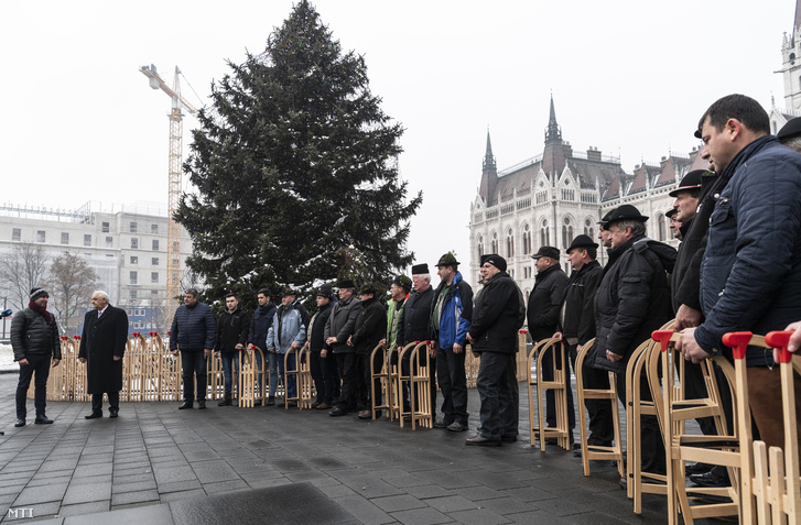 Latorcai János, az Országgyűlés kereszténydemokrata alelnöke (b2), Antal Tibor, a Gyimes Völgye Férfikórus kórusvezetője (b) és kórustagok az Ország Karácsonyfájánál a Kossuth téren 2018. december 21-én. A kórus tagjai tíz szánkót hoztak.