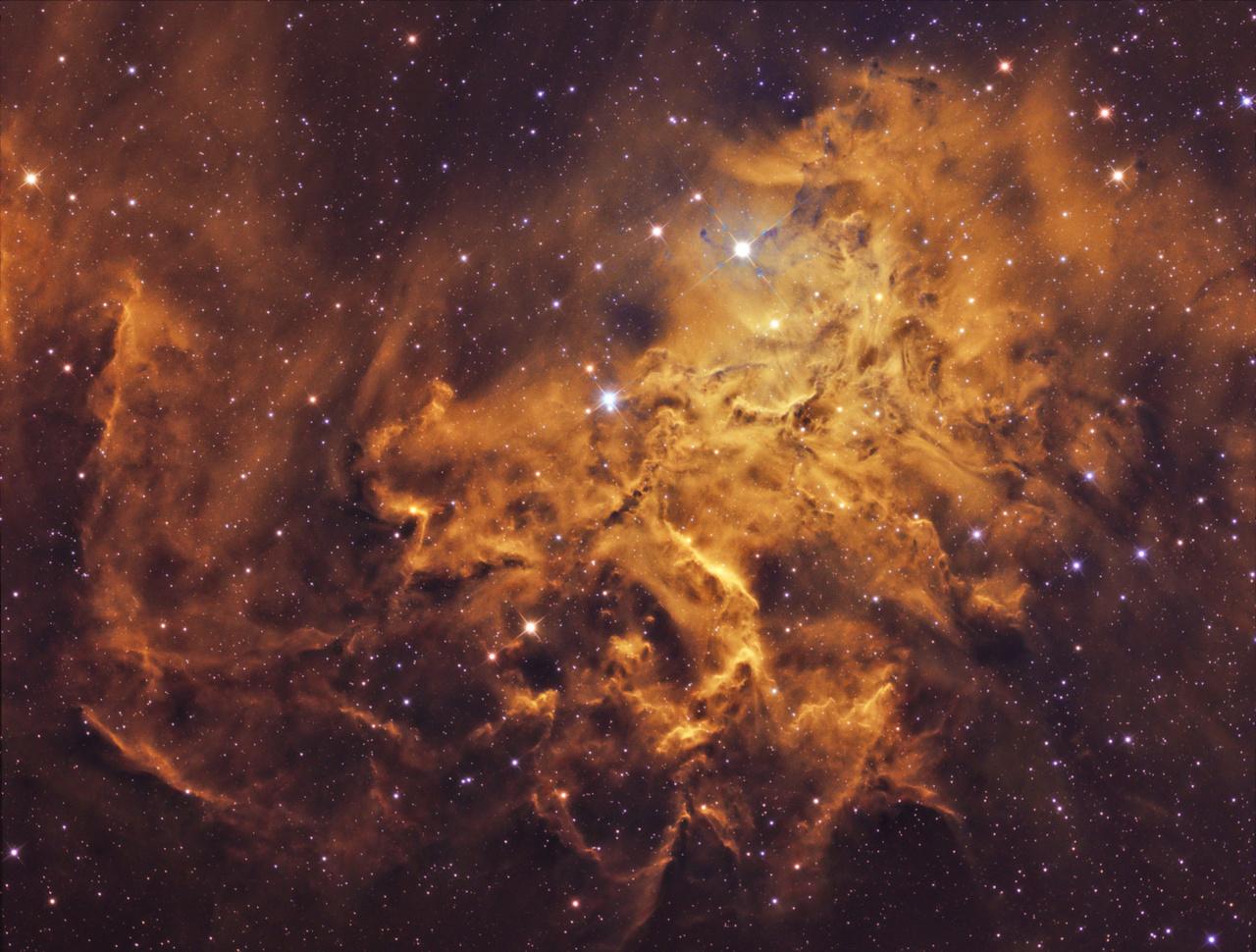 """""""Valami nagy-nagy tüzet kéne rakni."""" Ezen a fotón a Szekeres csillagkép szívében található diffúz köd, a Lángoló csillag-köd látható. Megjelenésében nagyon hasonlít a tűzhöz, lobogó lángnyelvekhez, innen a fantázia név. Ezt a látványt nagyban erősíti a HST, Hubble fotóknál is használt színpaletta, amelyet Bagi László kép elkészítésekor használt. A lángoló Csillag-köd Földünktől 1500 fényév távolságra található. A végleges fotó 28,5 óra expozíció eredménye."""