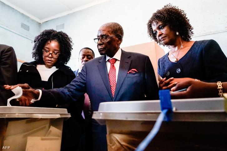 Robert Mugabe (középen) leadja a szavazatát a zimbabwei választásokon 2018. július 30-án, mellette lánya Bona (balra) és felesége Grace látható