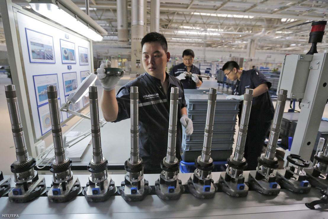 Kínai munkások a szerelőszalag mellett az Audi német autógyártó tiencsini sebességváltó-gyárában