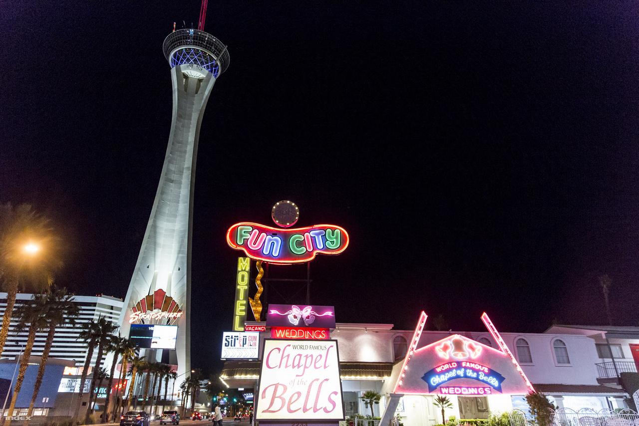 A Fun City Motel és a Chapel of the Bells házasságkötő kápolna neonfényei a Stratosphere torony közelben.