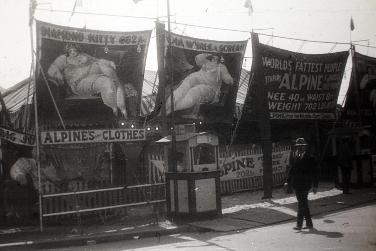 Diamond Kitty a kor egyik leghiresebb utazó cirkuszának, az 1906-ban alapított, évente több mint száz amerikai városba ellátogató Shrine Circusnak volt az egyik ikonikus mutatványa a Világ legkövérebb emberei című showban. Ezen a plakáton 702 fontosnak, azaz nagyjából 318 kilósnak és 20 évesnek írják, a Pinteresten találtunk egy plakátot, ahol 714 font (csaknem 324 kiló) volt az akkor állítólag 19 éves lány tömege. Azt nem tudni, hogy a cirkusszal melyik városban találkoztak a magyar utazók.