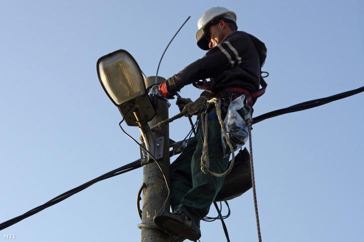 Egy villanyszerelő dolgozik a közvilágítás felújításán Vácon egy villanyoszlop tetején, 2013. november 8-án