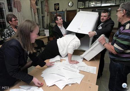 Választási biztosok kiürítenek egy szavazóurnát egy moszkvai szavazóhelyiségben