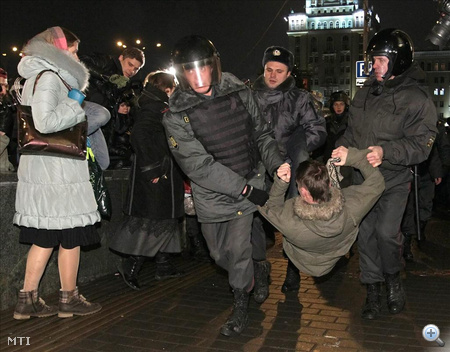 Orosz rendőrök letartóztatnak egy férfit, aki egy engedély nélküli tüntetésen vett részt a moszkvai Vörös tér közelében lévő bazársoron az oroszországi parlamenti választások napján.