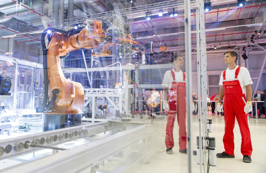 Dolgozó egy motor-összeszerelő robotnál az Audi Hungaria Zrt. új, elektromos motorokat gyártó győri üzemcsarnokában az avatás napján, 2018. július 24-én