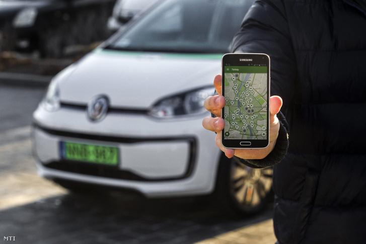 A közösségi autómegosztó szolgáltatás szabad autóit mutató alkalmazása egy telefon kijelzőjén Budapesten