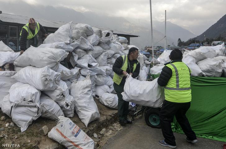 A Csomolungmán (Mount Everest) összegyűjtött hulladékot rakodják munkások a kelet-nepáli Lukla településnél működő Tendzing-Hillary repülőtéren 2018. március 17-én.