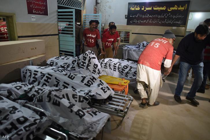 Pakisztáni önkéntesek viszik a buszbalesetben megégett holttesteket a halottasházba, Karacsiban 2019. január 22-én