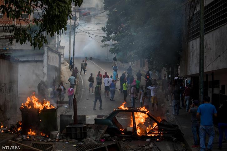 Tüntetők által emelt útakadály ég a nemzeti gárdisták egyik laktanyája közelében Caracasban 2019. január 21-én. A venezuelai különleges egységek a nap folyamán körülzárták a laktanyát, miután több nemzeti gárdista is megtagadta az engedelmességet a heves nemzetközi tiltakozások ellenére január 10-én beiktatott szocialista Nicolás Maduro elnöktől. A zendülők feladták magukat.