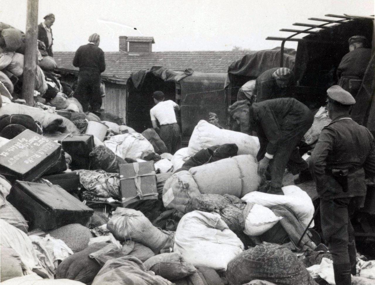 A táborba érkező zsidók személyes dolgait elvették, amiket a foglyoknak kellett a rámpáról összegyűjtögetni, majd azokat teherkocsik vitték az úgynevezett Kanada-szekcióba, ahol értékük szerint szortírozták őket. Attól fogva minden érték a Harmadik Birodalomhoz tartozott. Mire a munkával végeztek, a korábbi tulajdonosok legtöbbje már halott volt. A fenti képen egy SS-tag csípőre tett kézzel ügyeli a munkát.