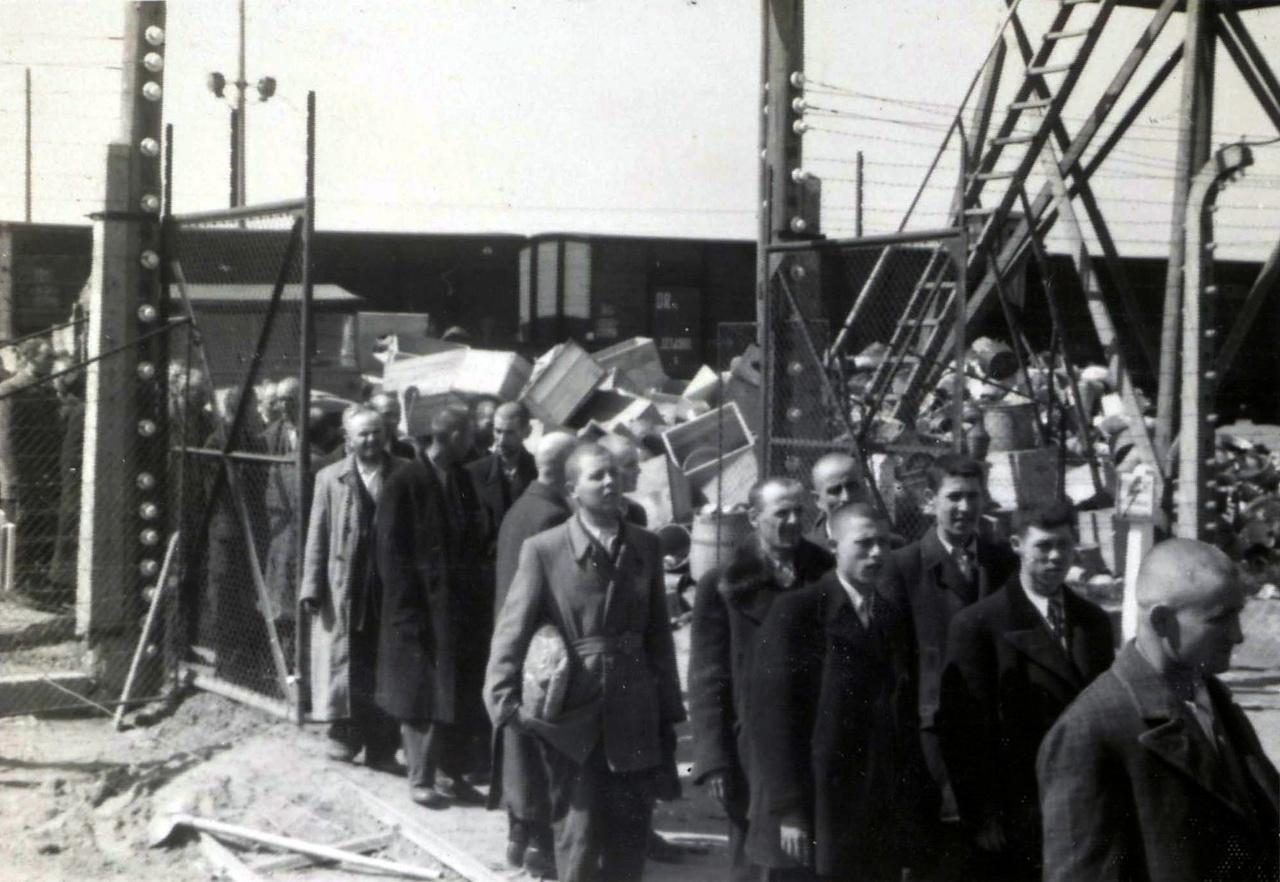 Zsidó férfiak, háttérben a vagonok és halomra pakolt zsidó-tulajdonok.