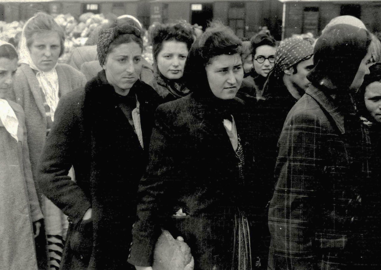 Az album magyar kiadása szerint a fotó közepén álló két nő, Rosenroch Sára és Falkovics Ráhel (feketében) túlélték Auschwitzot, majd Amerikában telepedtek le.