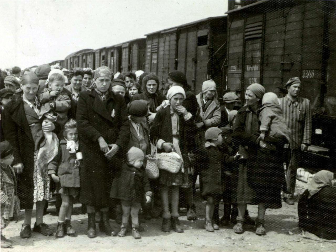 """Zsidó nők és gyerekek várakoznak a platformon. A kép jobb szélén álló csíkos rabruhás férfi a """"Kanada munkacsapat"""" egyik tagja, akiknek a tömeg irányításán kívül az is feladatuk volt, hogy összeszedjék a platformról az emberek holmijait."""