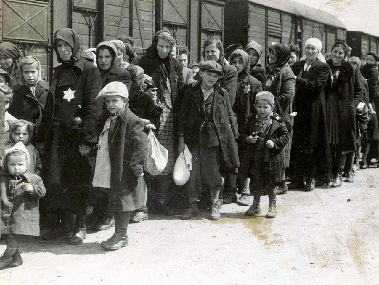 """Erről az időszakról az egyik SS-vádlott így beszélt a frankfurti Auschwitz-perben a hatvanas években: """"Auschwitz kihasználtsága 1944 tavaszán érte el a tetőpontját. Átlagosan tízezer ember érkezett naponta Birkenauba. Mindegyik krematórium teljes gőzzel működött. Ez ebben a formában eddig még Auschwitzban is példa nélkül állt"""", idézi őt Peter Moses-Krause az albumról írt tanulmányában. A fenti fotón néhányan az otthon sebtében bepakolt kis zsákokat fogják, még azt gondolhatják, szükségük lesz rájuk. A sárga csillag április 5-től kötelezően ott virít a ruhákon."""