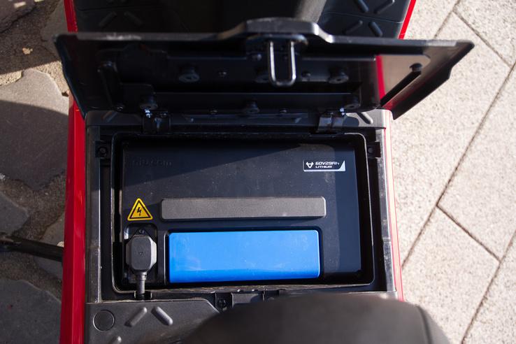 Az akkumulátor a taposó alatt van, és egy másik behelyezhető az ülés alá is. Egy mozdulattal kivehető, így ha a garázsban nincs áram, könnyen felvihető a lakásba