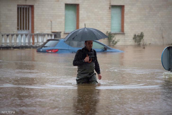 Árvízben elárasztott utcán gyalogol egy férfi az észak-spanyolországi Hinojedo településen 2019. január 24-én.