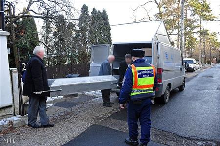 A temetkezési intézet dolgozói rendőrök jelenlétében a szállítójárműbe helyezik a koporsót