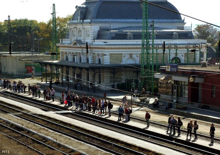 A Szent István Egyetemre Budapestről és környékéről bejáró egyetemistáknak népes csoportjai várakozik vonatra a város vasútállomásán.
