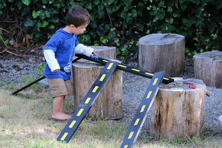 Variálható kerti autópálya lefestett deszkák és nagy farönkök segítségével.