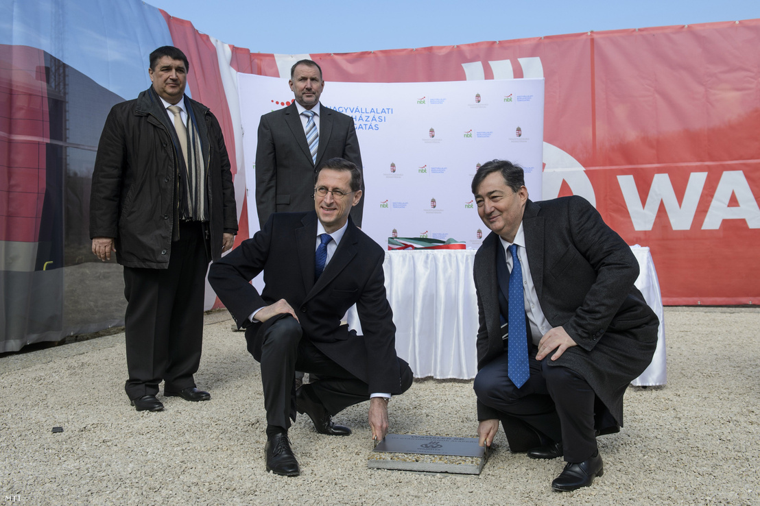 Minister of Economy Mihály Varga laying the foundation stone of a new factory subsidised by the state. Next to him, crouching on the right is Lőrinc Mészáros, the indirect owner.