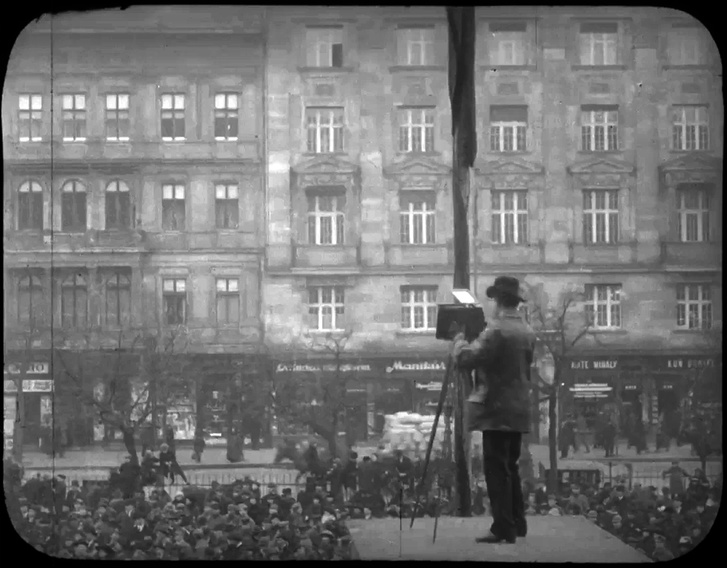 A Nemzeti Múzeum lépcsőpillérén álló fényképész Ady Endre dísztemetésén, 1919. január 29-én.