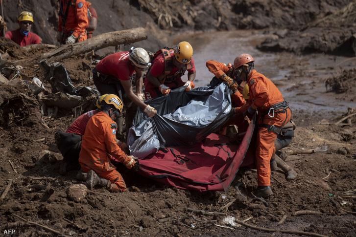 A helyi tűzoltóság tagjai egy áldozat holttestét emelik ki az iszapból Minas Gerais állambeli Brumadinho közelében 2019. január 28-án