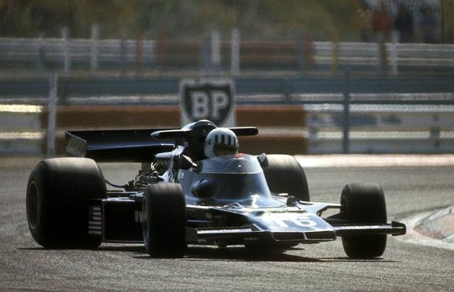 Tom Pryce sem volt piskóta, itt is finoman erőcsúsztat a Shadow DN5B-tel (1976). A walesi születésű Pryce villámgyors volt, esőben pedig verhetetlen, annak ellenére, hogy a DN5 nem volt valami jó konstrukció. Egyedüli Forma-1-es győzelmét 74-ben szerezte, de a Brands Hatch-en rendezett futam nem számított bele a világbajnoki pontversenybe. Korának Colin McRae-jeként emlékeznek rá ma is, aki mindig a maximumon túl teljesített. Halála a Forma-1 egyik nagy tragédiája volt. 1977-ben a Dél-Afrikai Nagydíj folyamán Renzo Zorzi autója kigyulladt és az akkor érvényes szabályok szerint két pályabírónak kellett oltania, míg szükség esetén másik kettőnek biztosítania őket. A pályán átfutó Frederik Jansen Van Vuuren-t Hans-Joachim Stuck még kikerülte, de az ő szélárnyékából érkező Pryce 270 km/órás sebesség mellett szó szerint kettévágta. Vuuren túzoltó-készüléke Pryce sisakjának csapódott és Pryce azonnal életét vesztette. Az ütközés erejéről mindent elmond a tény, hogy az eldeformálódott tűzoltókészülék átrepült a lelá