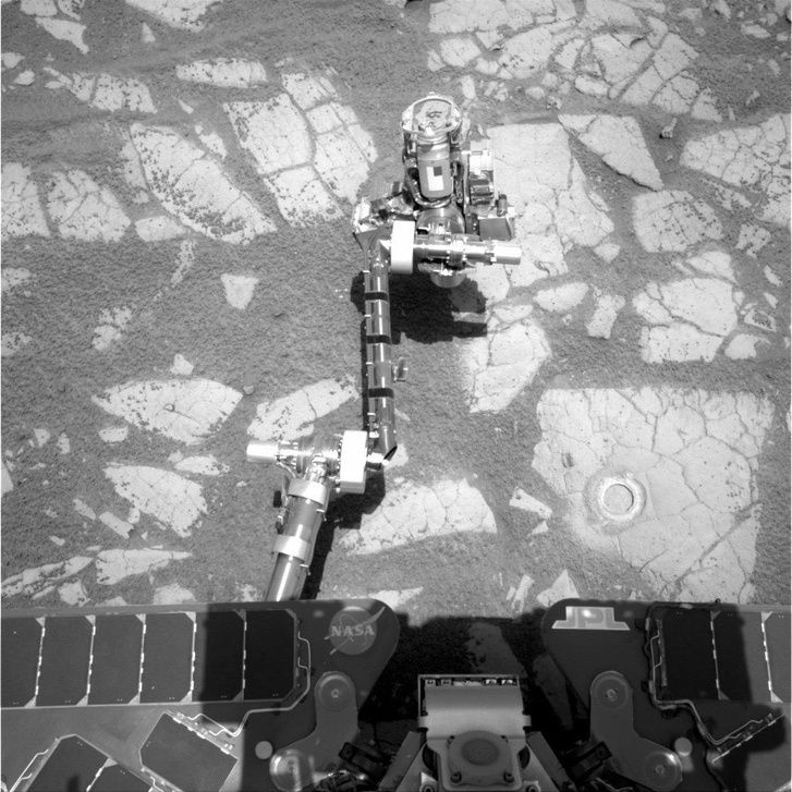 Az Opportunity robotkarja kőzetmintát vesz.
