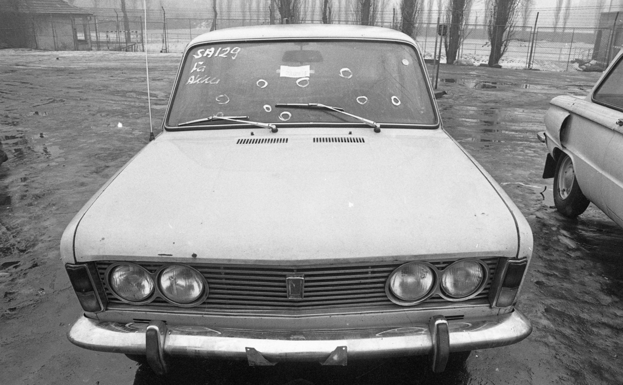 Egy Polski Fiat 125P. Ha hinni lehet a szélvédőn lévő feliratnak, az akkuval gondok voltak. A szélvédő sérüléseit (kavicsfölverődés) bekarikázták, hogy más baja volt-e az autónak már csak az adásvltel megkötése után derült ki. Az árcédulán 33 000 Ft áll, azaz tízhavi átlagkeresetbe került használtan a lengyel személygépkocsi-gyártás olasz licenszű zászlóshajója. Jobbra egy Zaporozsec fara lóg be.
