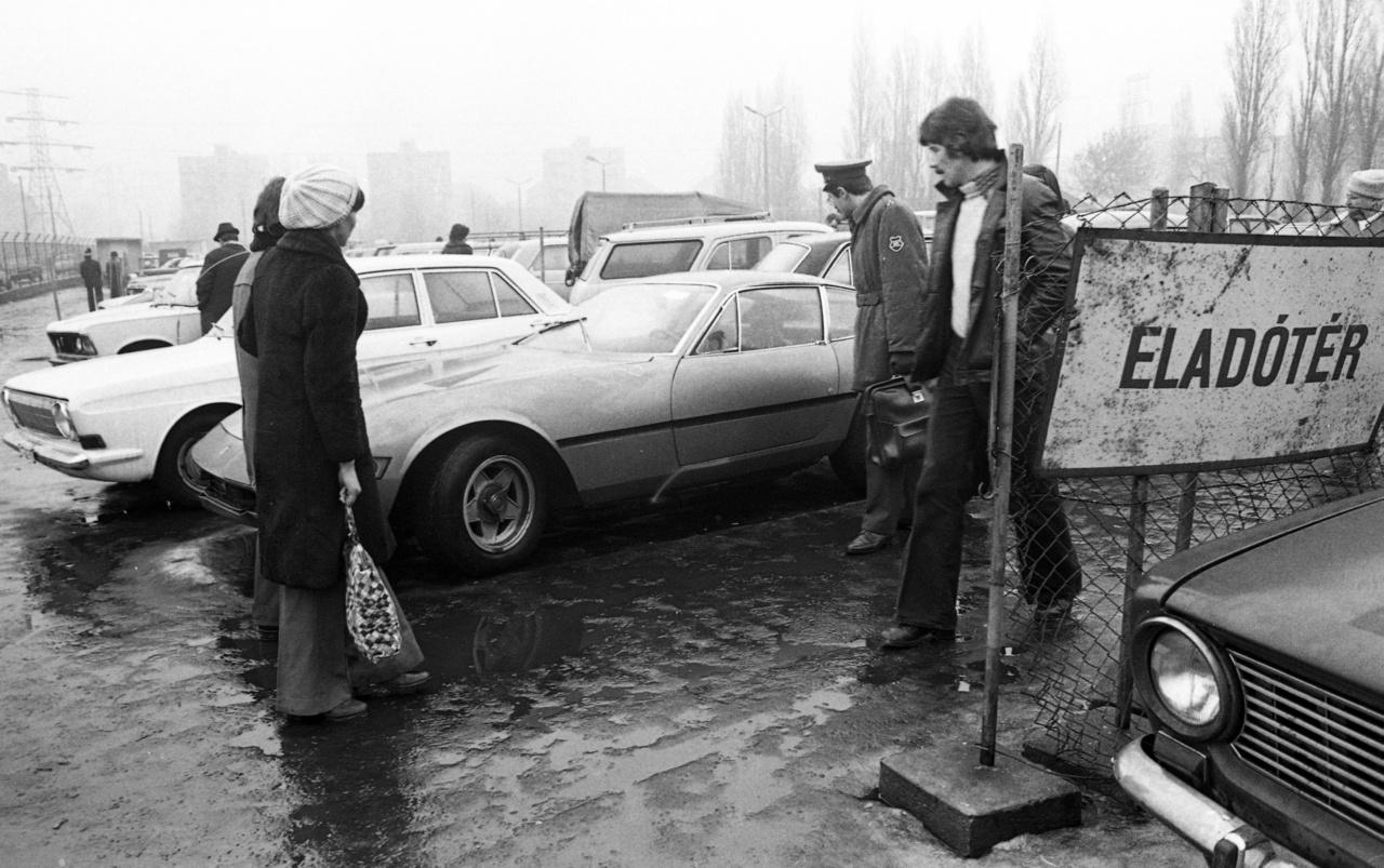 """És akkor álljunk meg egy pillanatra és csodáljuk meg ezt fényképet és az autót, amit rajta láthatunk. Mert az egyszer biztos, hogy ilyen eladó használt autót még a Néphadsereg tisztjei se sűrűn láttak a hetvenes évek Magyarországán. Ez bizony egy Ferrari 365 GTB/4 """"Daytona"""". Ha minden igaz, 1974-es évjáratú, és az Autó-Motor hetilap használt autós rovata szerint 1977. júniusában kelt el 190 ezer forintért. (1977-ben 3413 Ft volt az átlagkereset, 2017-ben 297 017 Ft, ha amatőr közgazdászként vesszük, ma áron 16,5 millió forintot érne a 40 évvel ezelőtti vételár). A Daytonákra manapság elég nagy a gyűjtői kereslet: évjárattól és állapottól függően 700 ezer dollár (200 millió forint) körüli árakon kelnek el autós aukciókon. A legkevesebb amit mondhatunk, hogy valami elképesztően szürreális látványt nyújt a hideg angyalföldi sárban tündöklő olasz autócsoda."""