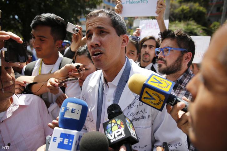 Juan Guaidó (k) nyilatkozik a sajtónak a támogatói körében a Nicolás Maduro hivatalban levő venezuelai elnök elleni tüntetésen Caracasban 2019. január 30-án
