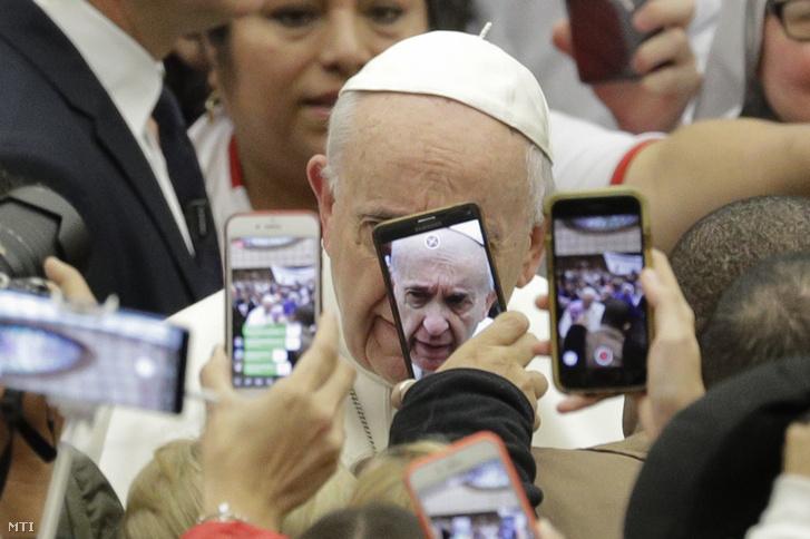 Hívők fotózzák mobiltelefonjaikkal a heti általános audienciájára érkező Ferenc pápát a Vatikán VI. Pál pápa termében 2019. január 9-én