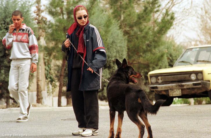 Egy nő kutyát sétáltat Iránban.