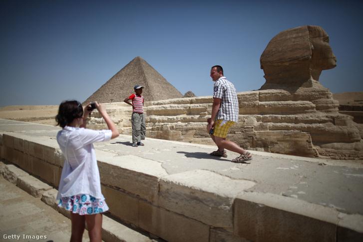 Turisták fotózkodnak a gízai piramisok és a szfinx mellett
