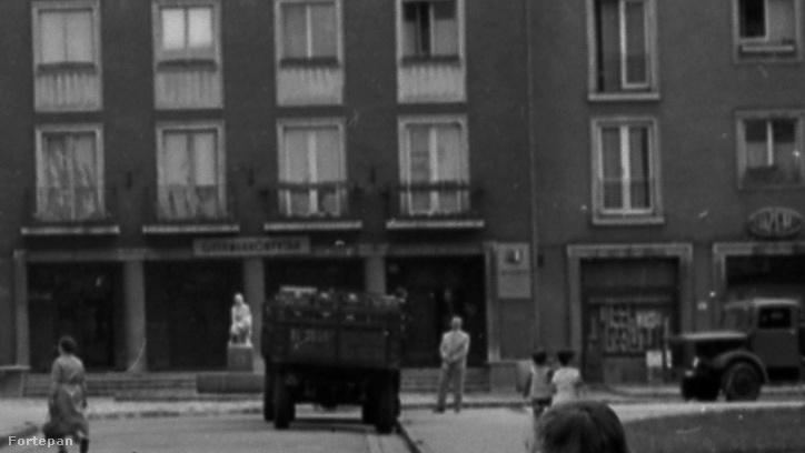 A kinagyított képrészleten fel lehet ismerni a Közért-feliratot a jobb szélen. A teherautókon alighanem épp a boltba érkezett áru