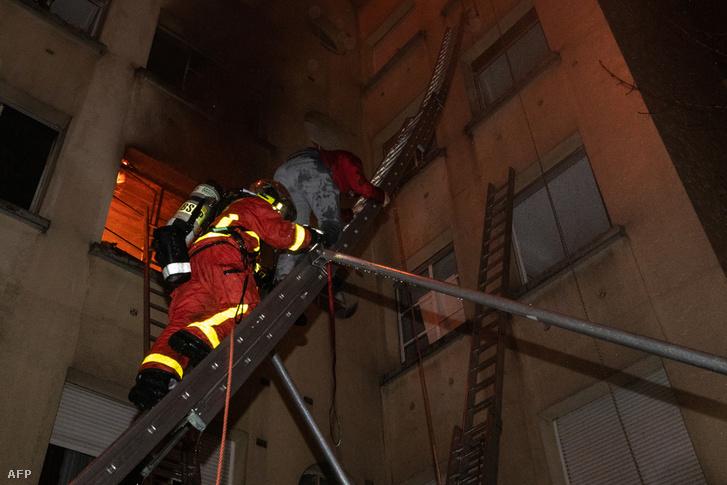 Tűzoltó és egy lakó mászik le a létrán a kigyulladt házból