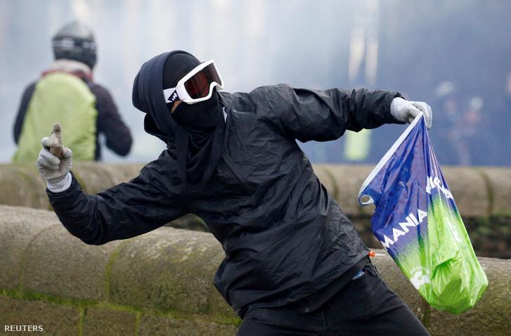 A sárgamellényes tüntetéseken köveket dob a rendőrök felé egy tüntető Franciaországban