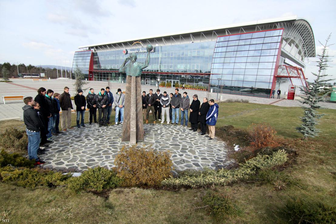 Az MKB Veszprém KC kézilabdázói és a csapat vezetői mécseseket gyújtanak a Marian Cozma emlékére felállított mellszobránál a Veszprém Aréna előtt 2013. február 8-án.