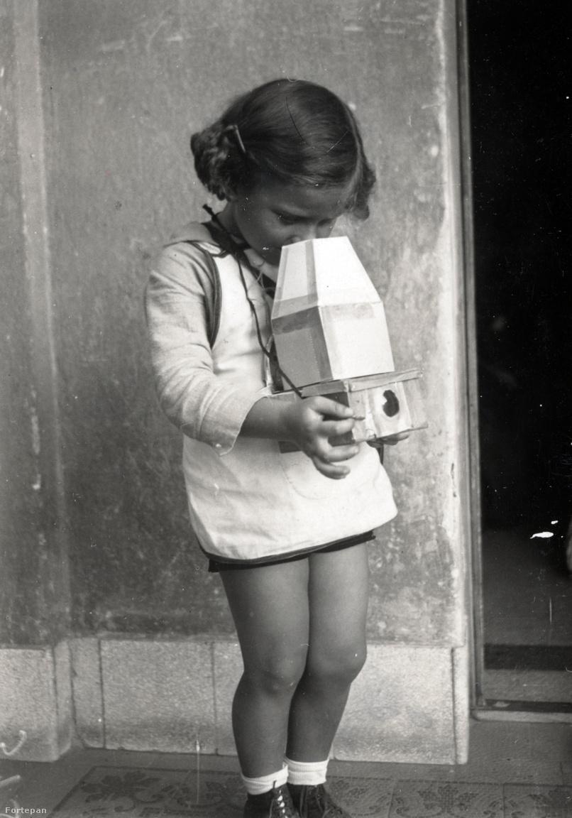 Gábor talán két évesen, az apjától kapott játék fényképezőgéppel.Kinszki rengeteget játszott a gyerekekkel. A játékpuska, ólomkatona, íj ki volt tiltva, de volt helyette kisvasút, saját készítésű állatos meg őslénytanos társasjáték, papírból hajtogatott és kifestett város hidakkal, házakkal, épületekkel, kupolával. Gabi papírból készített fényképezőgépet is kapott, benne rajzokkal, mintha ő fotózta volna.