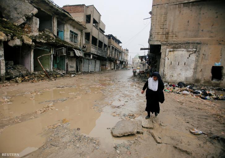 Nő sétál Moszulban a romok között 2019. február 2-án
