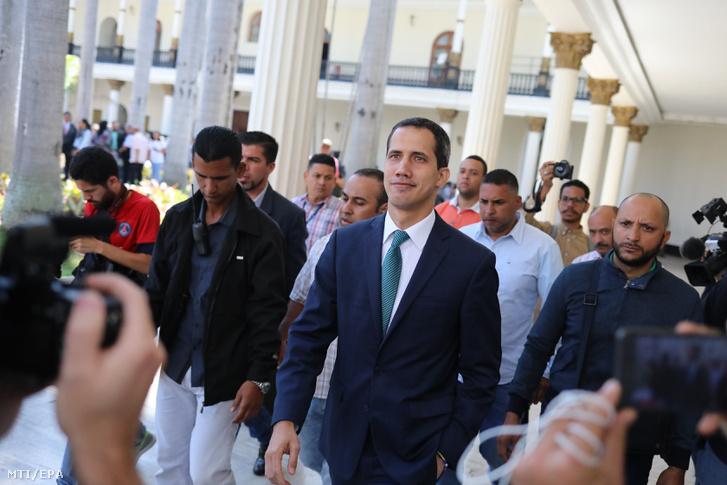 A magát ideiglenes venezuelai államfőnek nyilvánító Juan Guaidó, az ellenzéki többségű venezuelai parlament vezetője (k) sajtóértekezletre érkezik a nemzetgyűlés caracasi épülete előtt 2019. február 4-én.