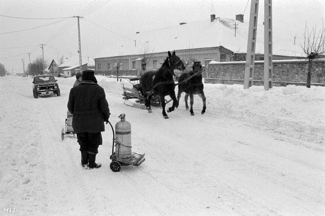 Zirc, 1987. január 14. Lovas szánon és gyalogosan közlekednek az emberek a havas úton, kézikocsin tolják a PB-palackot. Veszprém megyében az utak többségét méteres hófalak szegélyezik, így gyakran egy nyomsávra szűkülnek az utak.