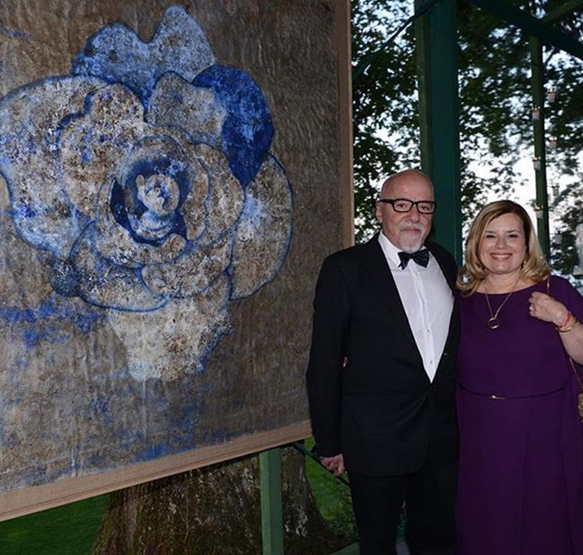 Christina Oiticica elismert brazil képzőművész, kiállításaira gyakran elkíséri őt férje. A háttérben a hölgy egyik művészeti alkotása látható.