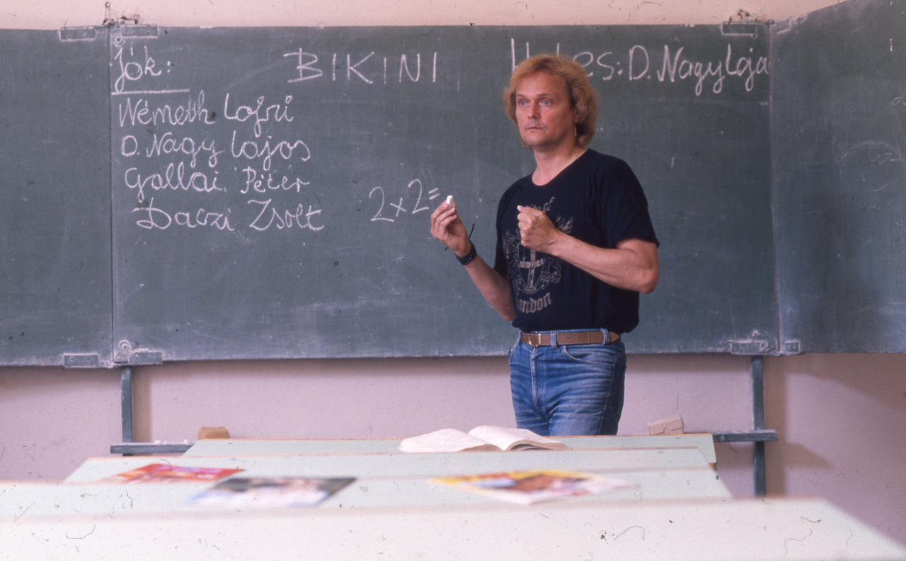 """Ha már D. Nagy Lajos és a Bikini, itt egy iskolai tanórát megidéző fotó a Nagy Ferót váltó énekesről. A képről leginkább onnan lehet tudni, hogy már a rendszerváltás idején készült, hogy a táblán a """"jók"""" között szerepel Daczi Zsolt neve is, aki már a '80-as évek végén csatlakozott a zenekarhoz gitárosként."""