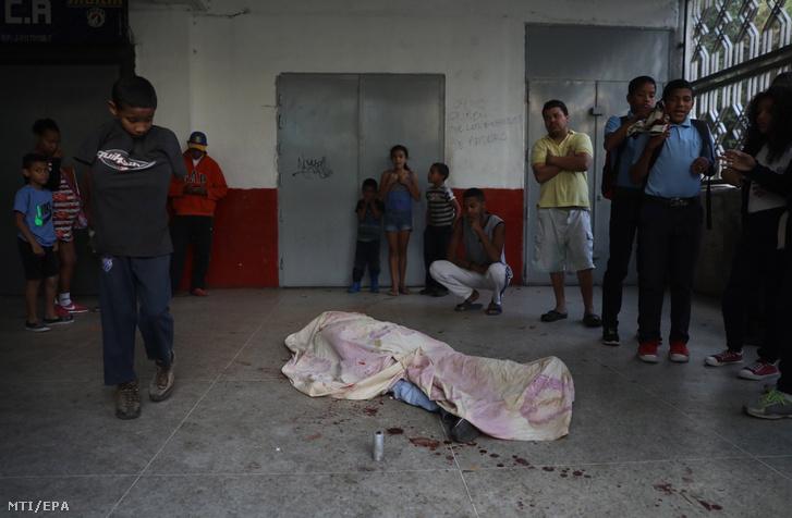 Letakart holttest hever a földön a kormányellenes tüntetők és rohamrendőrök összecsapása után Caracasban 2019. január 23-án.